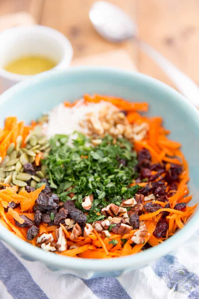 Grated carrots, raisins, cranberries, pecans, walnuts, pumpkin seeds, parsley and coconut in a blue bowl
