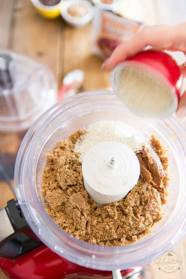 Shredded coconut is being added to the bowl of a food processor that already contains date paste, ground cashews and chestnuts