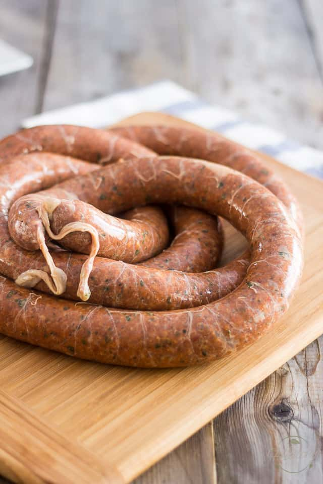 A single long link of Homemade Italian Sausage twisted on a wooden cutting board