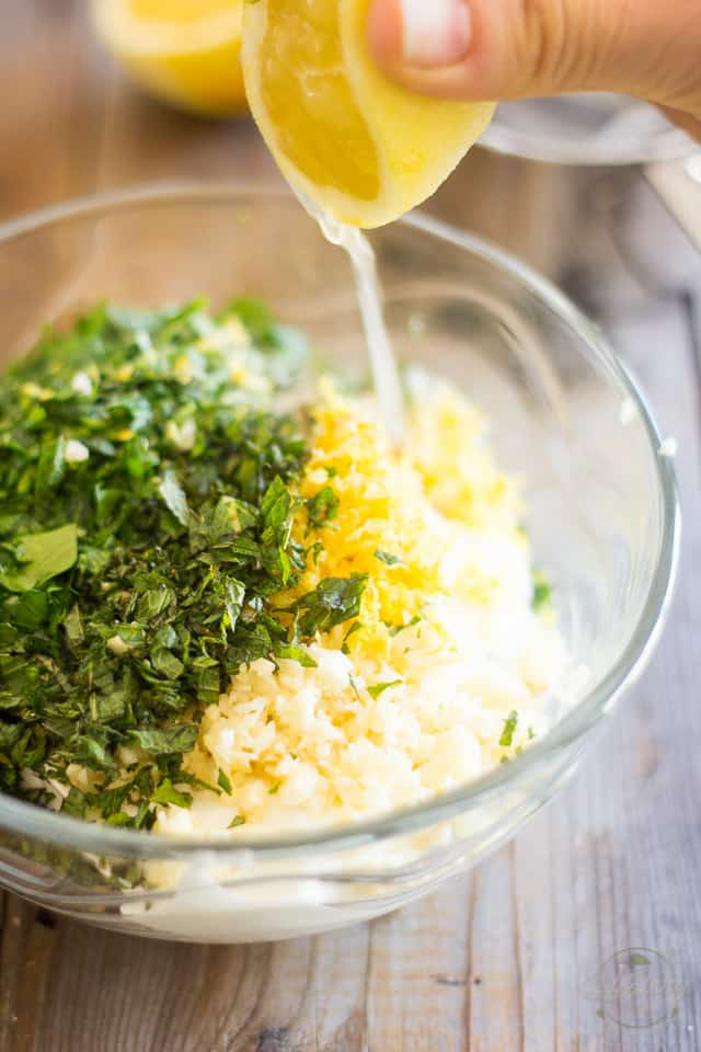 Lemon juice getting squeezed in bowl containing yogurt and chopped herbs