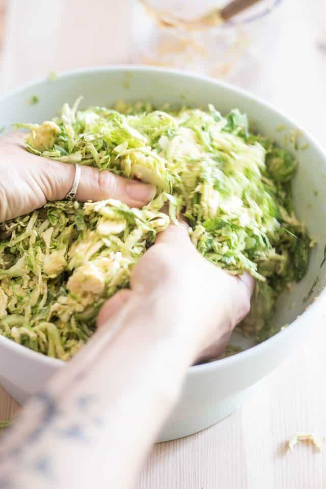 Mixing the Shaved Brussels Sprouts and Dressing | thehealthyfoodie.com