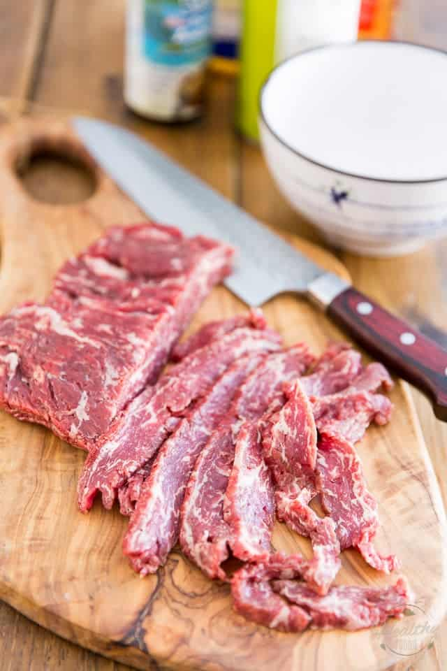A piece of flank steak partly sliced on a wooden cutting board with a knife next to it
