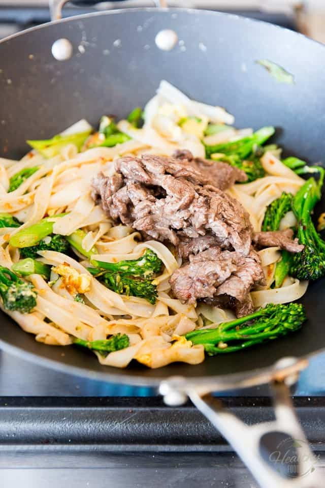 Thin slices of cooked beef are sitting on top of a pile of cooked rice noodles with broccolini, green onions and scrambled eggs in a black non-stick wok
