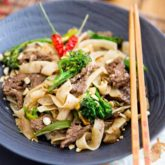 A serving of beef pad see ew in a black bowl, garnished with a couple of birds eye peppers with a pair of chopsticks resting on the rim of the bowl