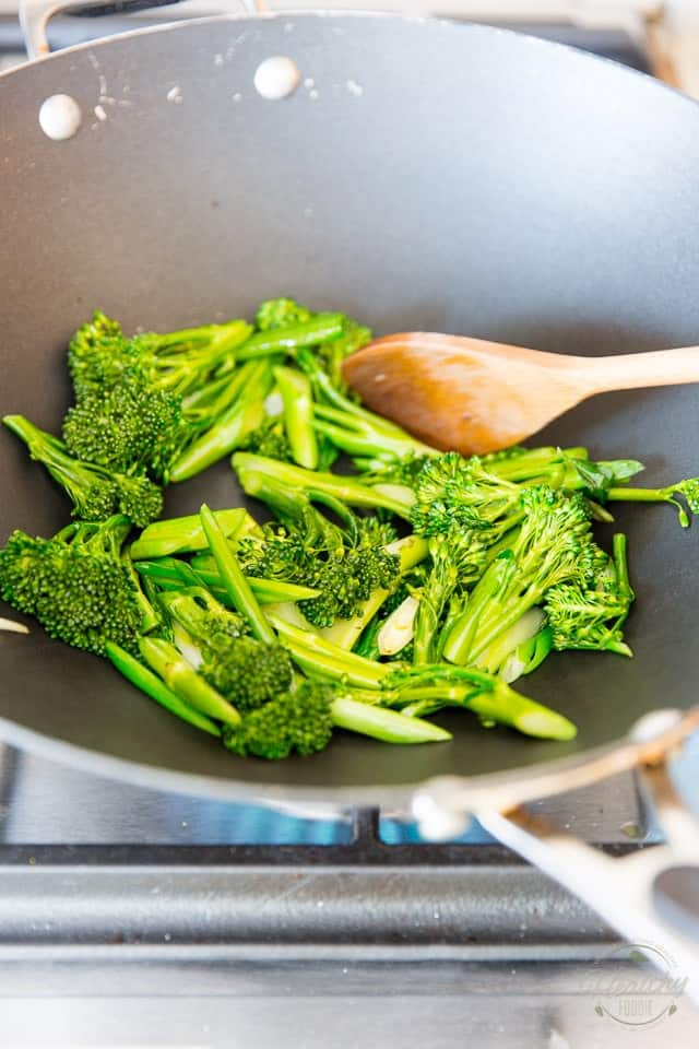 Broccolini and green onions being cooked and stirred with a wooden spoon in a non-stick wok