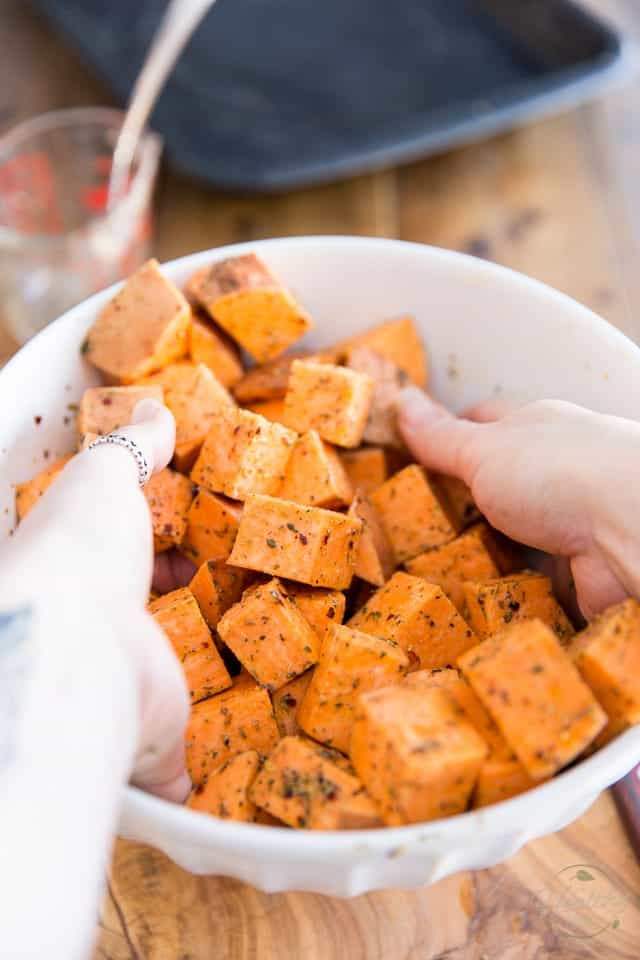 Tossing the sweet potatoes until evenly coated with the seasonings