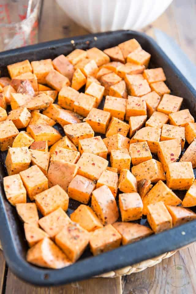 Sweet potatoes arranged in a single layer onto a roasting pan