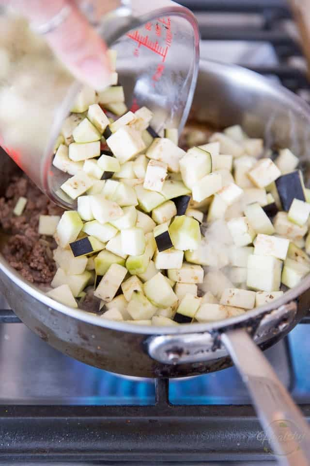 Diced eggplant gets added to the pan