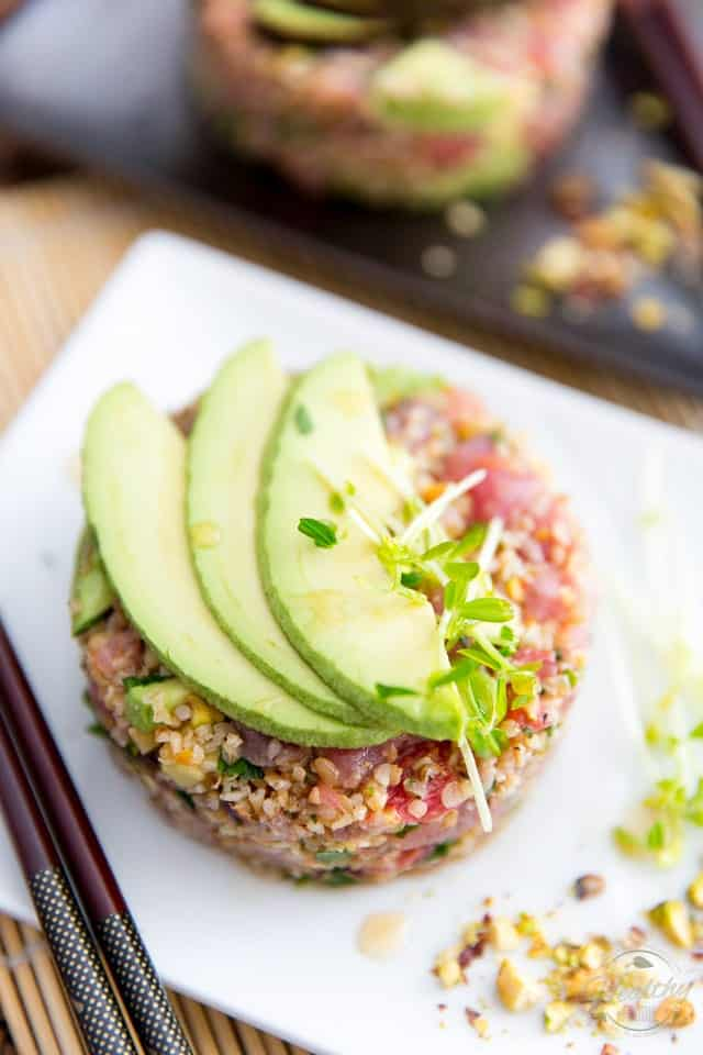 Overhead shot of Tuna Bulgur Tartare in a white plate topped with 3 thin slices of avocado and a pinch of microgreens, with a pair of chopsticks and a handful of chopped pistachios on the side