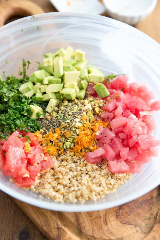 Bulgur, tuna, avocado, grapefruit and various herbs and spices in a large semi-transparent glass bowl