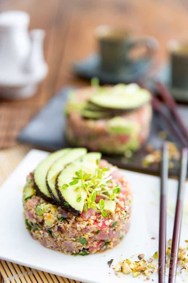 Tuna Bulgur Tartare in a white plate topped with 3 thin slices of avocado and a pinch of microgreens, with a pair of chopsticks and a handful of chopped pistachios on the side