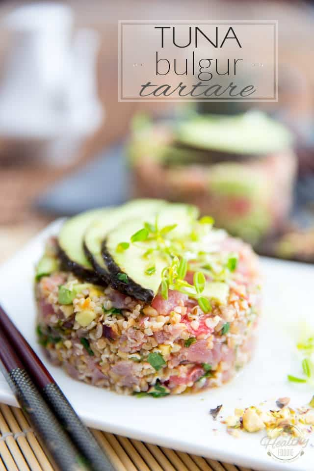 Tuna Bulgur Tartare in a white plate topped with 3 thin slices of avocado and a pinch of microgreens, with a pair of chopsticks and a handful of chopped pistachios on either side