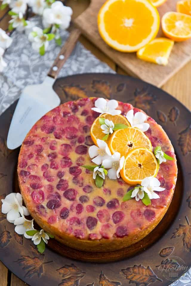 The finished Upside-Down Cranberry Orange Cake sitting in a dark brown cake plate, garnished with slices of orange and pretty white flowers
