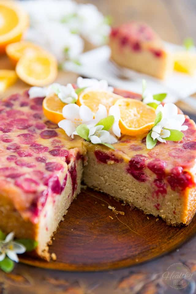 The finished Upside-Down Cranberry Orange Cake garnished with slices of orange and pretty white flowers, sliced open.