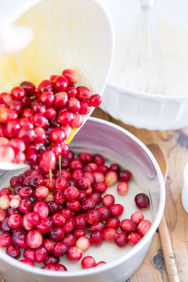 Fresh cranberries mixed with orange juice and honey being poured out of a white bowl and into an aluminum cake pan