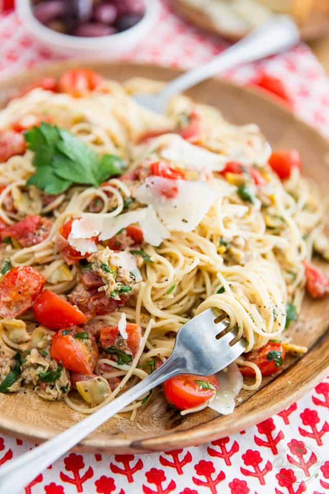 Angel hair pasta with cherry tomatoes, clams and fresh parsley served in a wooden plate with two forks and placed on top of red and white tablecloth