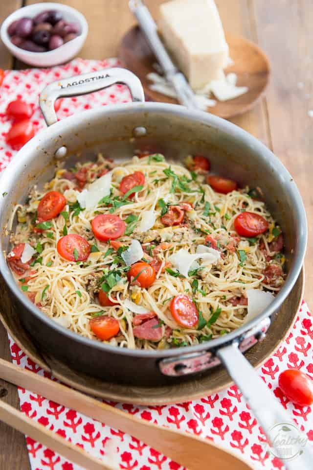 Angel hair pasta with cherry tomatoes, clams and fresh parsley displayed in a stainless steel saute pan on top of red and white tablecloth