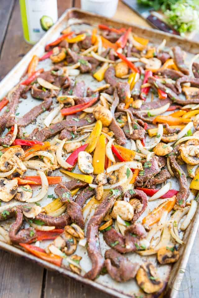 Strips of beef, bell peppers onions and mushroom arranged on a large aluminum baking sheet