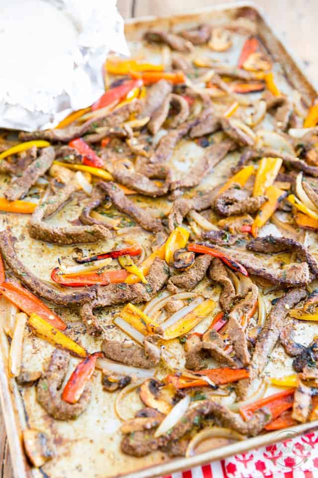 Strips of cooked beef, bell peppers onions and mushroom arranged on a large aluminum baking sheet