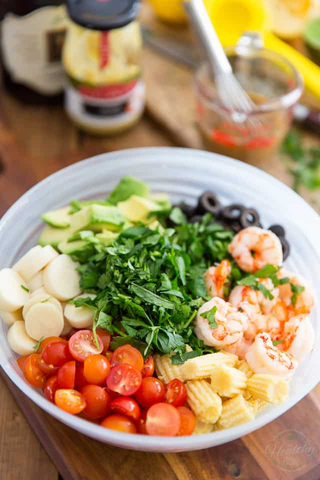 Cooked shrimp, cherry tomatoes, baby corns, hearts of palm, diced avocado, sliced black olives and parsley in a semi-transparent glass bowl