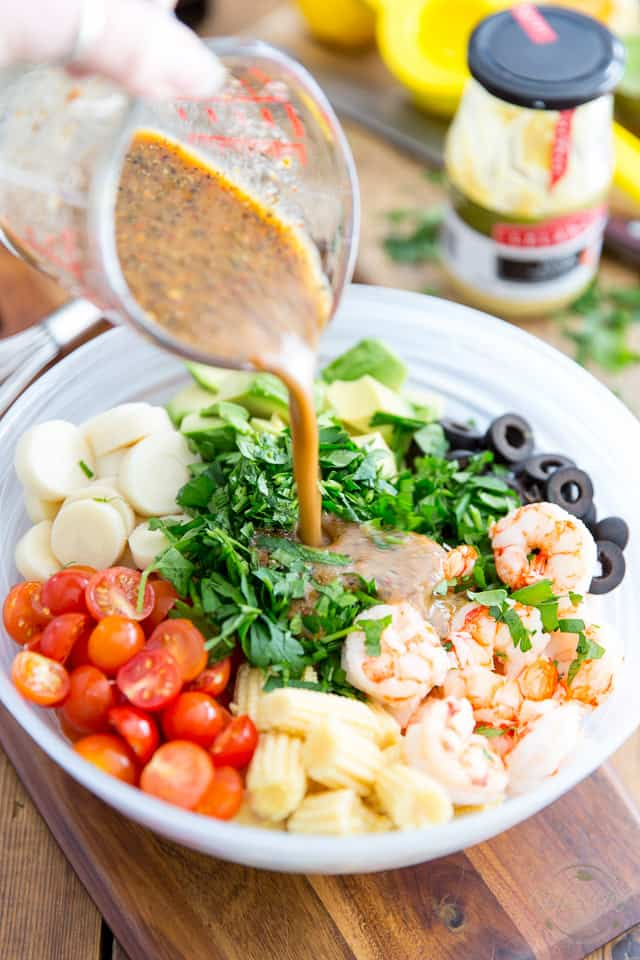 A vinaigrette is being poured out of a glass measuring cup and into a semi-transparent glass bowl containing cooked shrimp, cherry tomatoes, baby corns, hearts of palm, diced avocado, sliced black olives and parsley