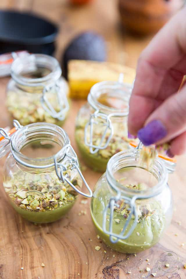 Little glass containers with avocado mousse in them, with pistachios getting sprinkled on top of one of the jars
