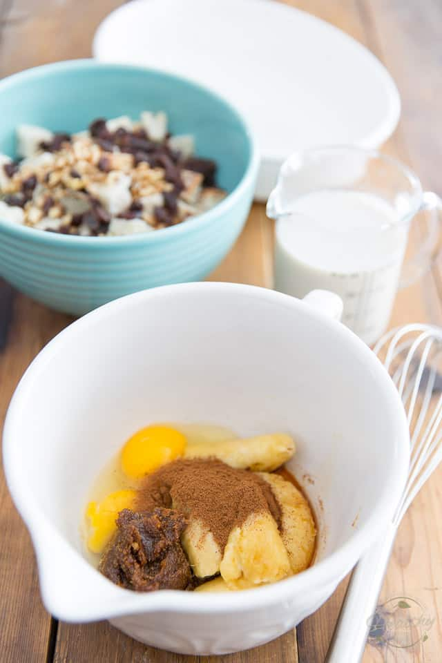 Ripe bananas, eggs, date paste and cinnamon in a white bowl in the foreground, a blue bowl containing cubed bread, walnuts and raisins in the background, as well as a cup containing milk