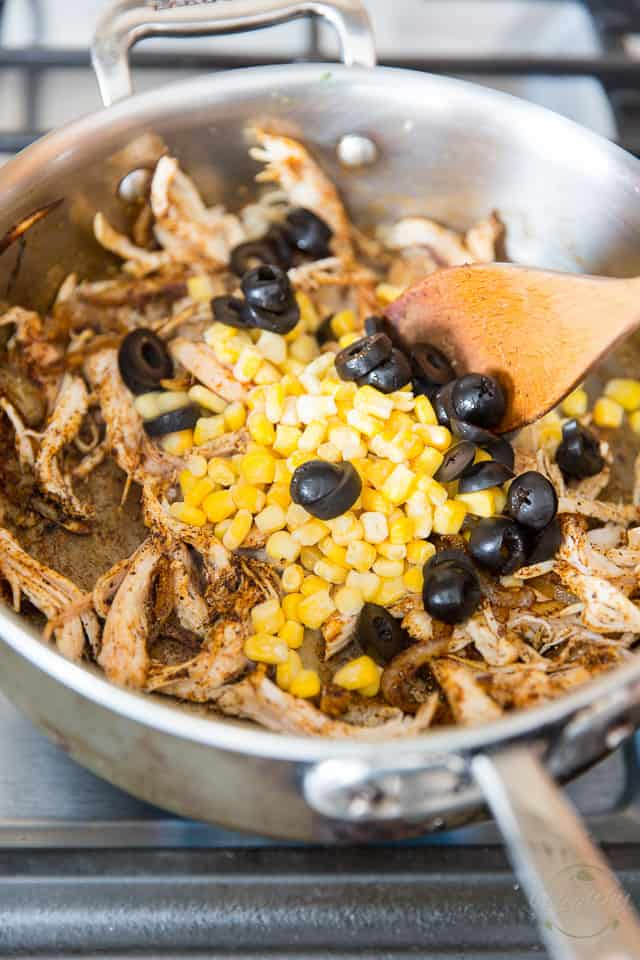 Sliced black olives, corn, chicken and sauteed onions in a stainless steel saute pan