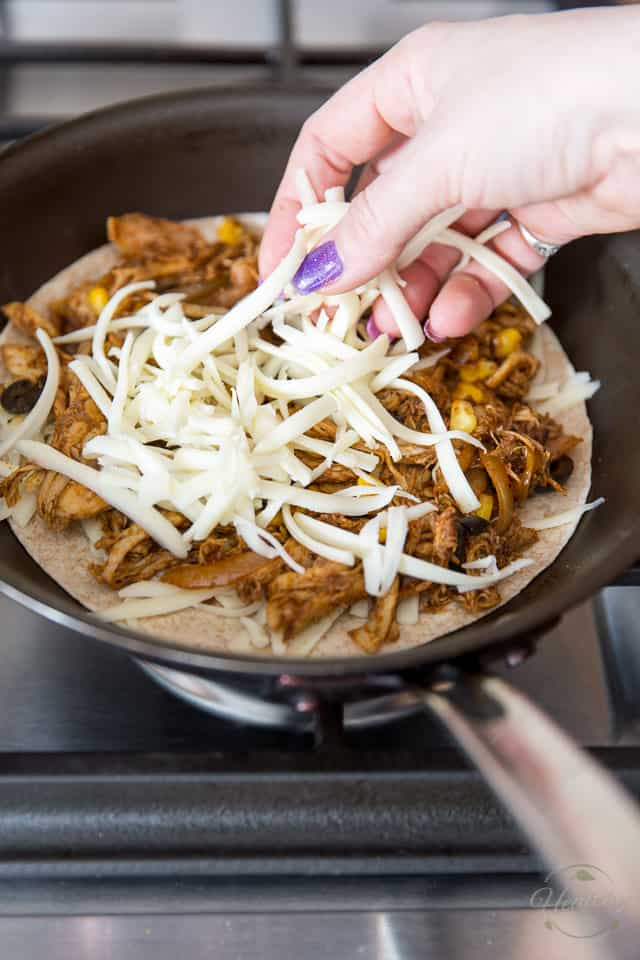 The final layer of cheese is being added to a Chicken Quesadilla cooking in a non-stick skillet