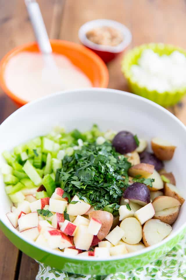 Cooked potatoes, apples, celery and parsley in a green bowl