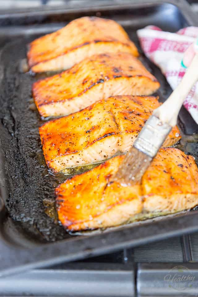 Cooked salmon fillets in a dark roasting pan getting brushed with honey glaze