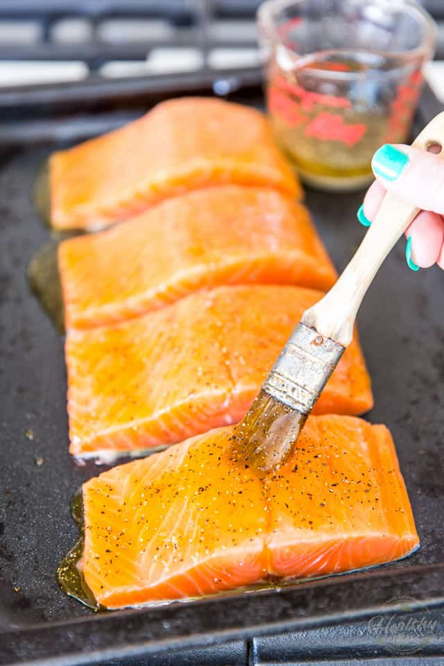 Salmon fillets in a dark roasting pan getting brushed with honey glaze