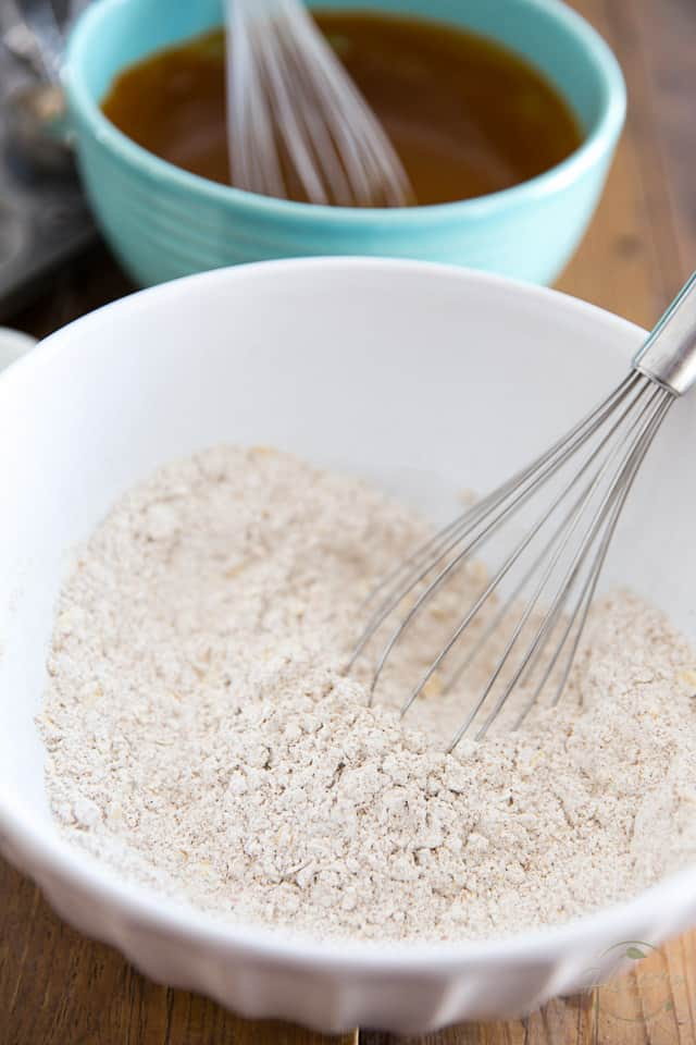 A white bowl containing a combination of whole wheat flour, rolled oats and spices, with a whisk resting on the side of the bowl