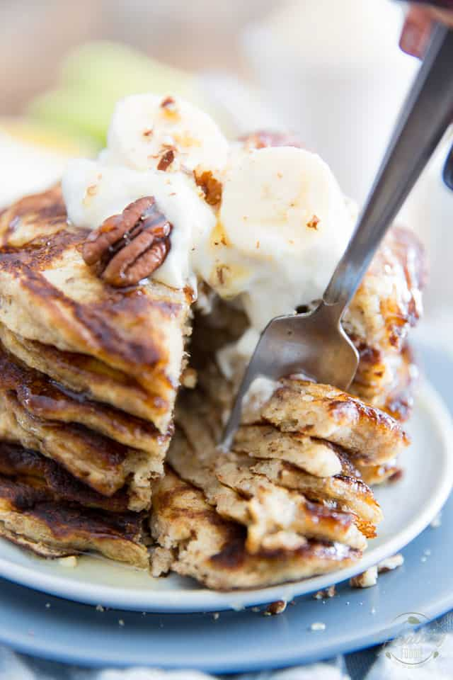 A stack of banana buttermilk pancakes topped with plain yogurt, banana slices, pecans and a little bit of honey