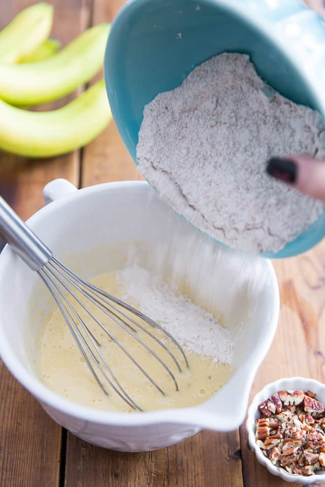 Flour is getting poured into a mixture of bananas, buttermilk, eggs and vanilla
