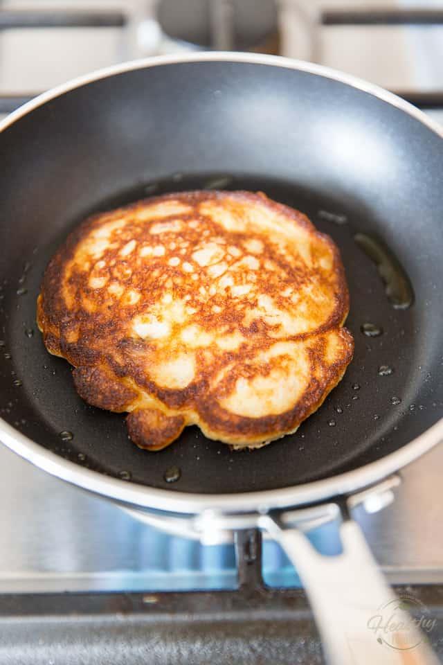 A banana buttermilk pancake in a small non-stick skillet