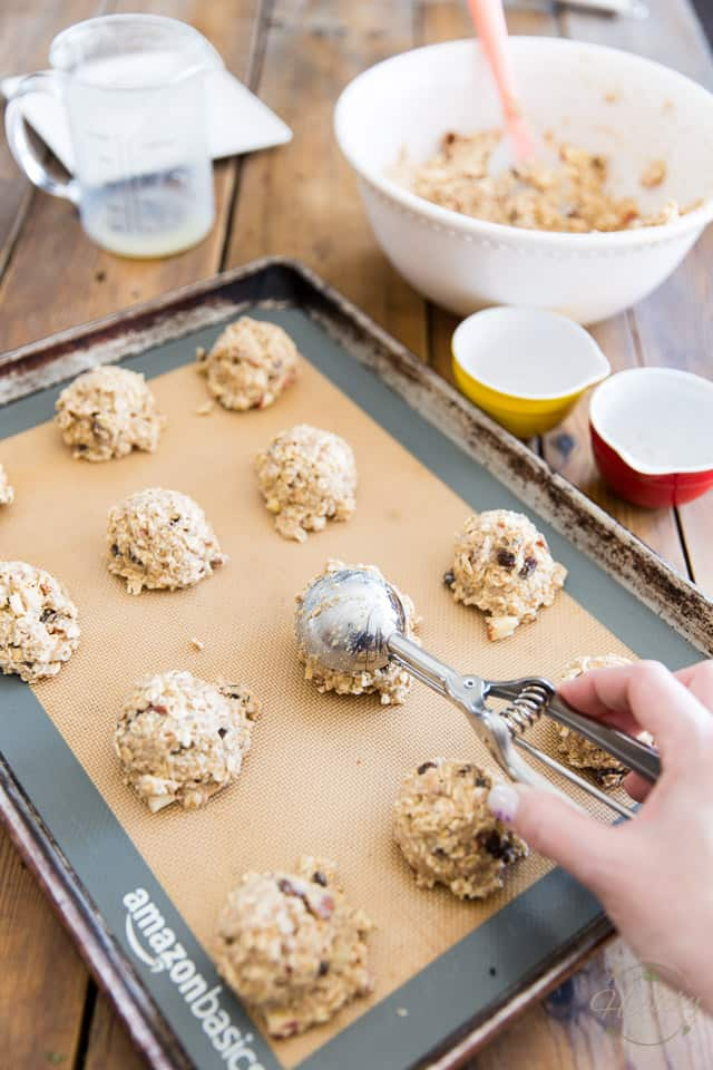 Oatmeal Cookie Dough is getting dropped out of a spring loaded scoop and onto a cookie sheet