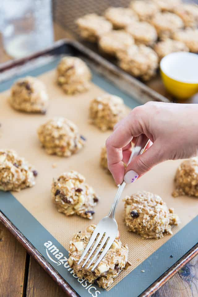 Baked cookies coming out of the oven are getting pressed down lightly with a fork