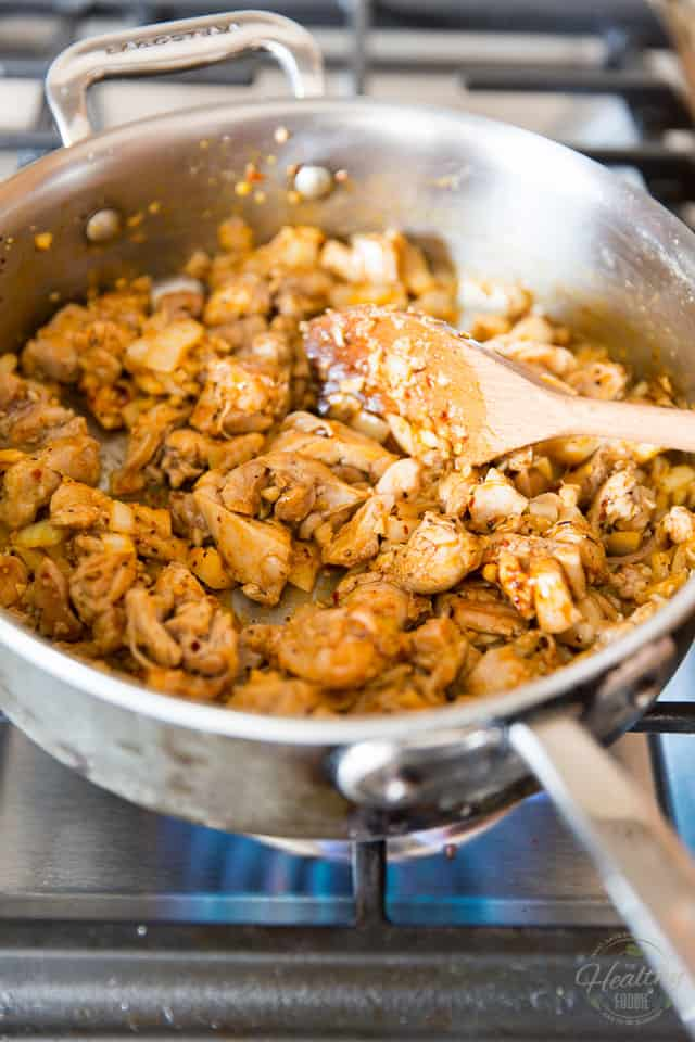 Pieces of chicken cooking in a stainless steel saute pan