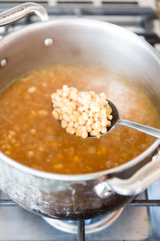 Cooked navy beans lifted from their cooking liquid with the help of a large stainless steel spoon