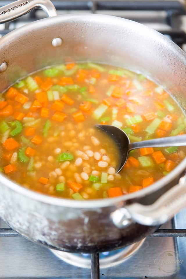 Navy beans, carrots and celery cooking in a large stock pot in a rich ham broth