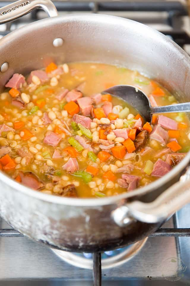 Cubed ham is getting stirred into a stock pot containing cooked navy beans, carrots, celery and stock