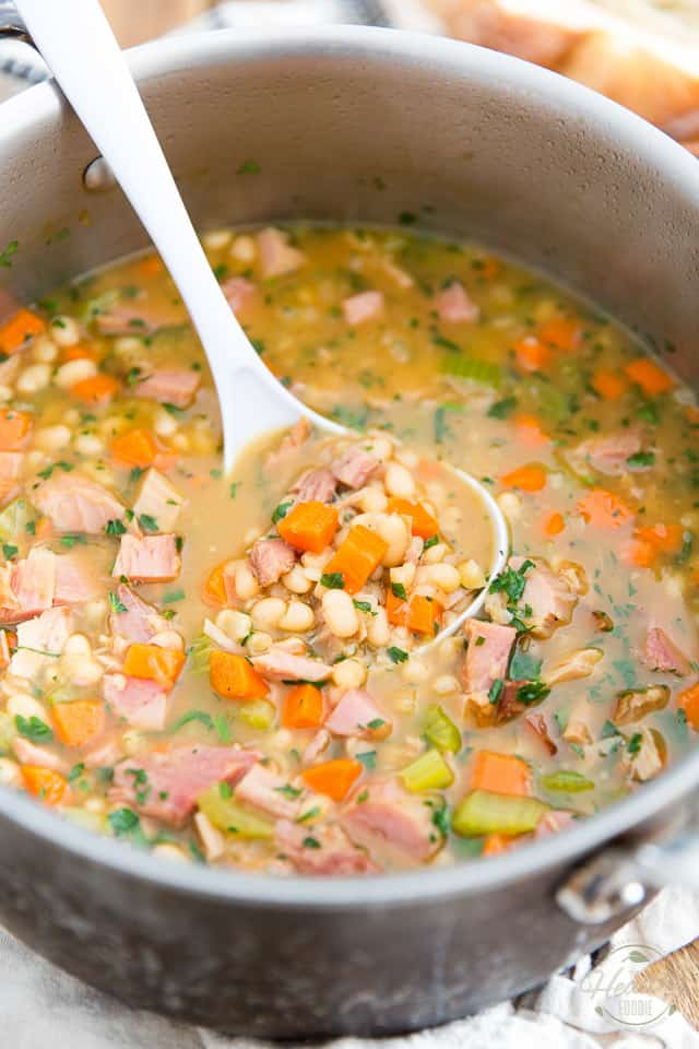 A large stock pot containing White Bean and Smoked Ham Soup with a white plastic ladle resting in it