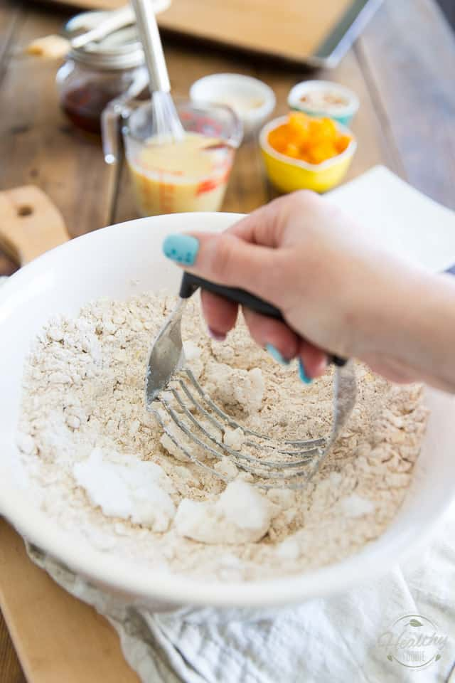Coconut oil is being mixed into flour mixture with pastry blender