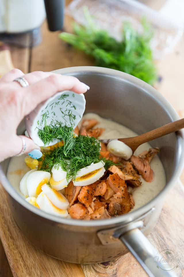Fresh dill, sliced hard boiled eggs and cooked salmon added to a stainless steel pot containing cauliflower sauce