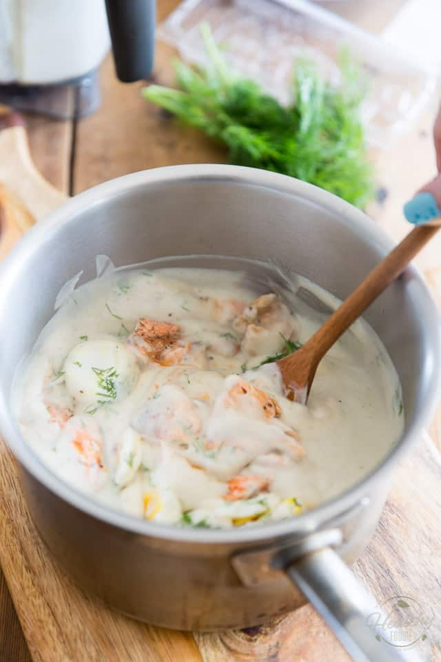 A rich and creamy cauliflower sauce with generous pieces of salmon and hard boiled eggs in a stainless steel saucepan