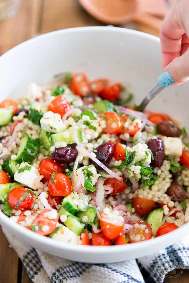 Greek Style Pearl Couscous Salad getting tossed with large spoon