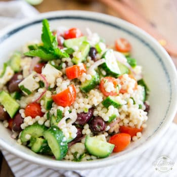 Loaded with tomatoes, cucumbers, feta cheese and kalamata olives, this Greek Style Pearl Couscous Salad is super refreshing, bursting with flavor and sure is a nice twist on your traditional Greek Salad! Bound to become a favorite this summer...