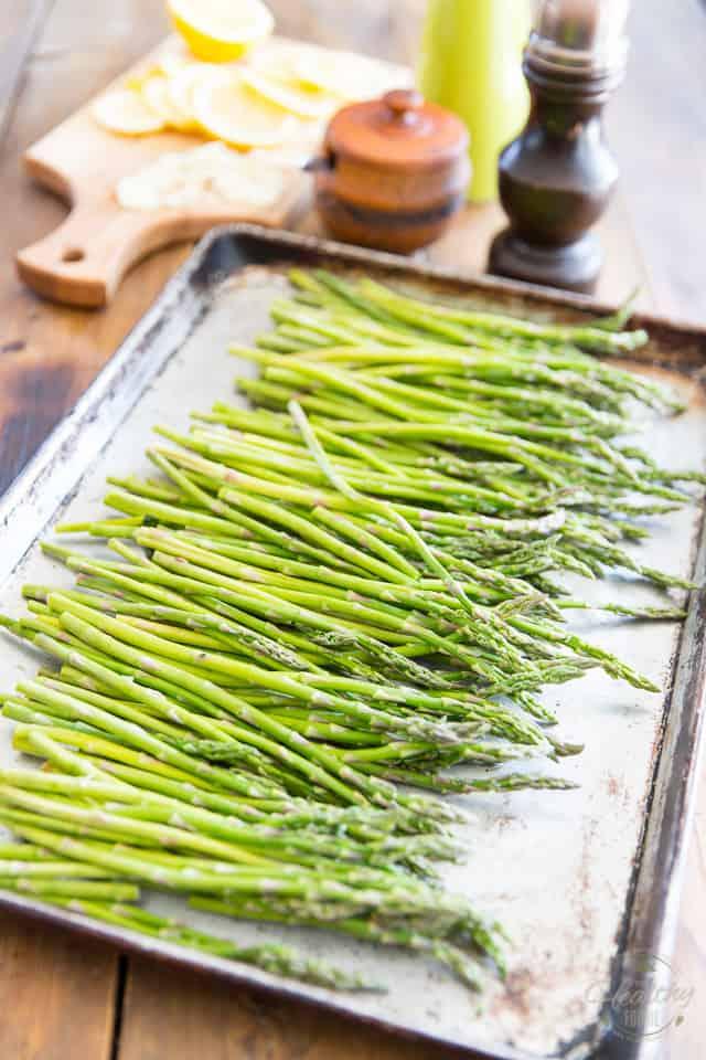 A pile of fresh asparagus in an aluminum baking sheet