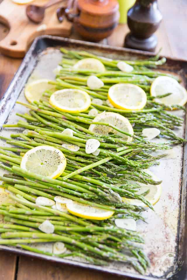 Asparagus with slices of lemon and garlic in an aluminum baking sheet